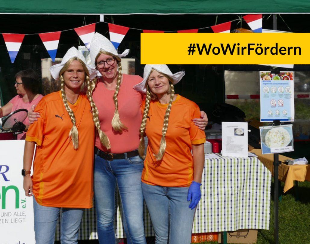WoWirFördern: Suppenfest in Greiz, Frauen in Kostümen vor einem Stand mit niederländischen Flaggen